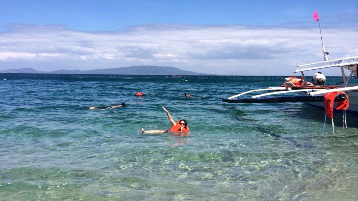 バタンガスのビーチで泳ぐ女性