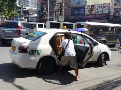 タクシーに荷物を詰め込む人