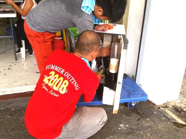コーヒー自販機に殺虫剤をスプレーする人