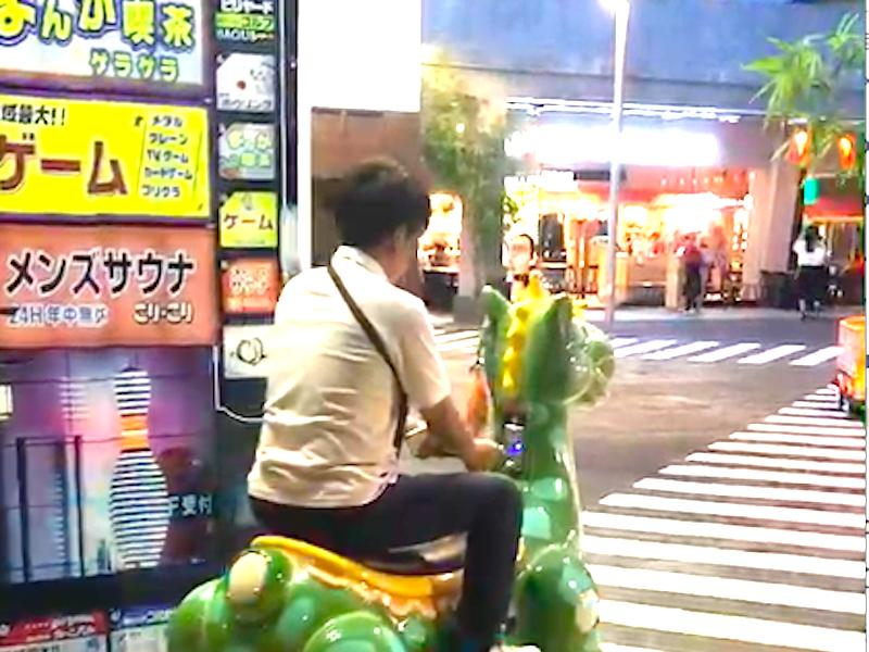 恐竜の乗り物に乗る日本人