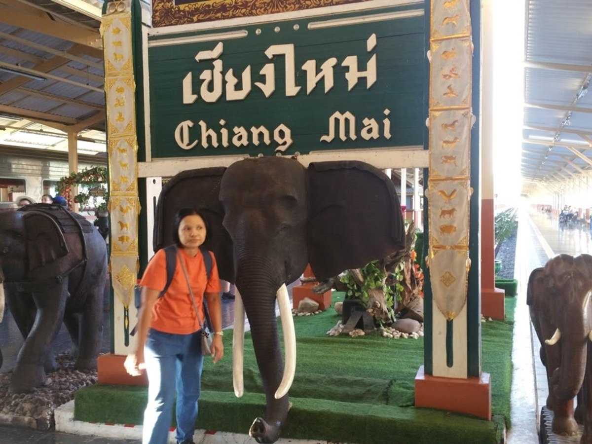 チェンマイ駅の象の前の女性