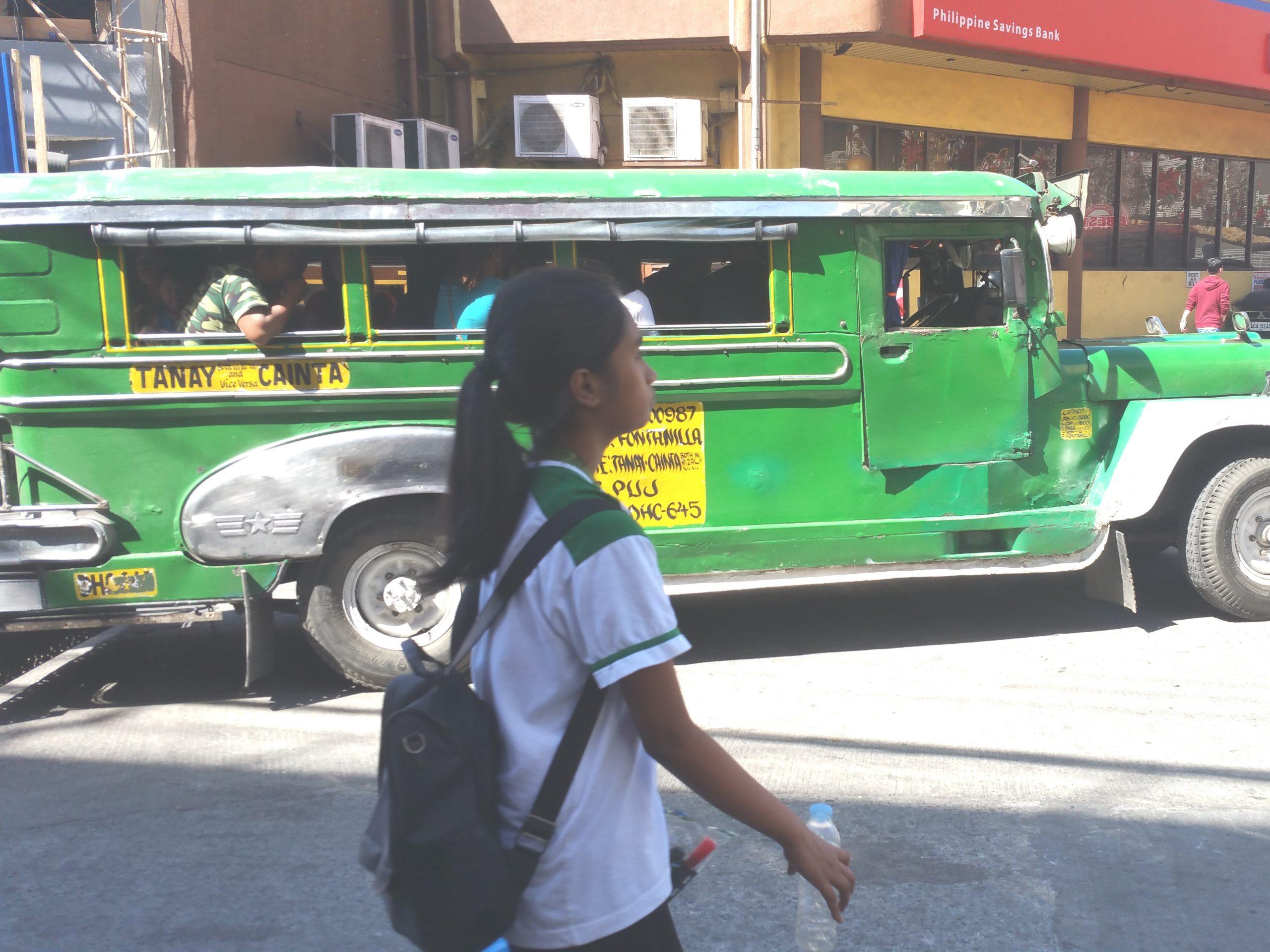 ジープニーの横を通る少女