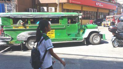 ジープニーの横を通る学生