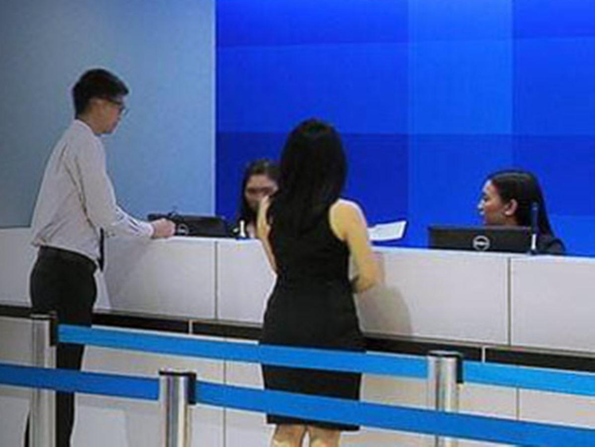 銀行カウンターに並ぶ女性